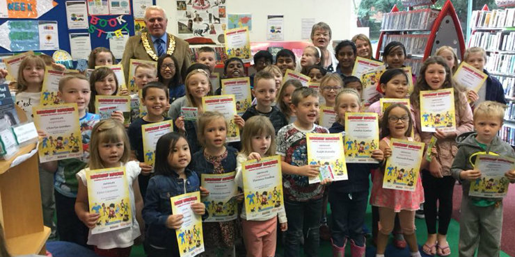 Children at Haverhill Library receive their Summer Reading Challenge certificates and medals from Mayor Tony Brown and library manager Audrey Woodley.