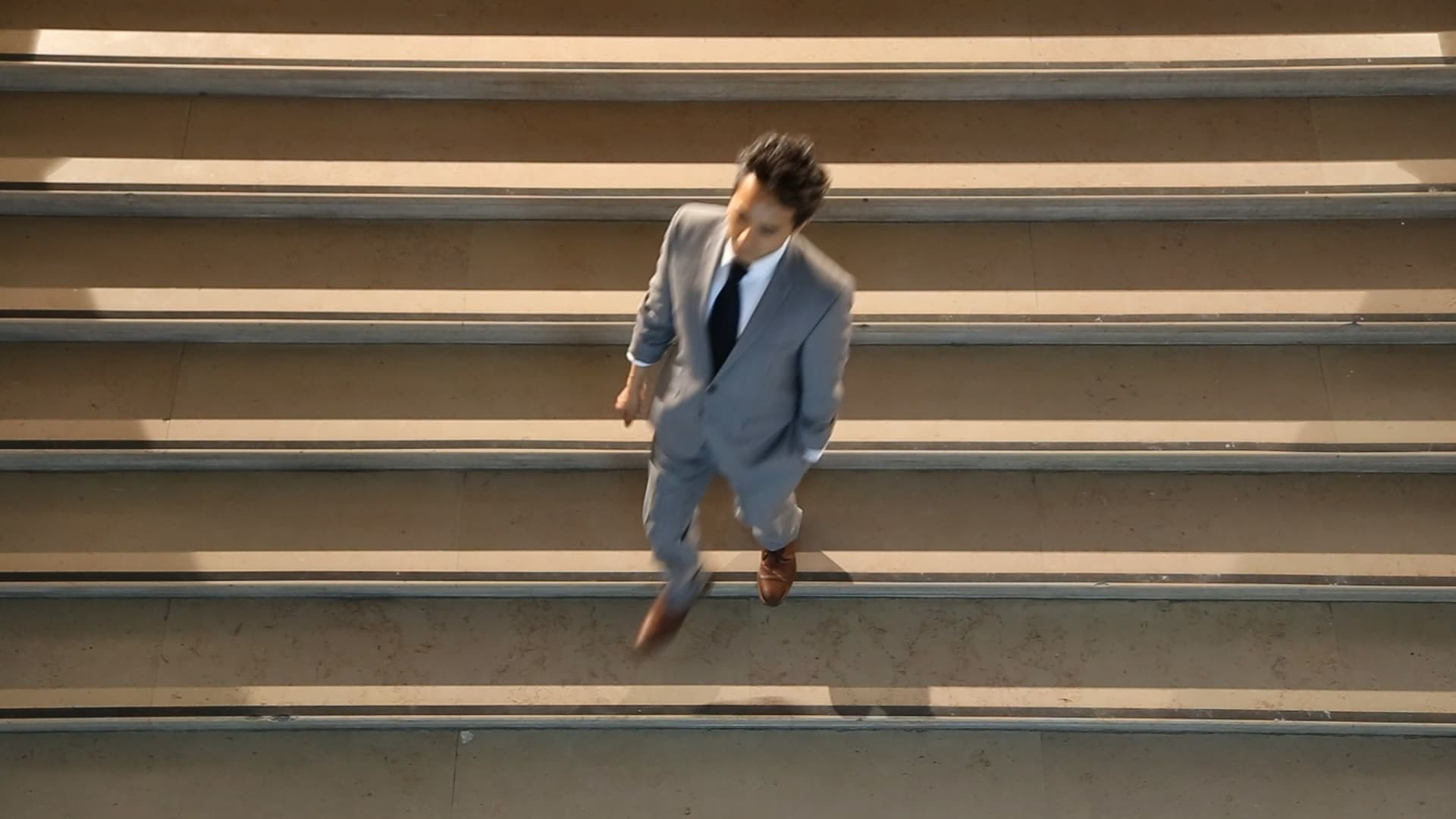 Still from the film Network/Intersect, by Ollie Palmer. The image depicts a businessman in a suit descending a flight of stairs.