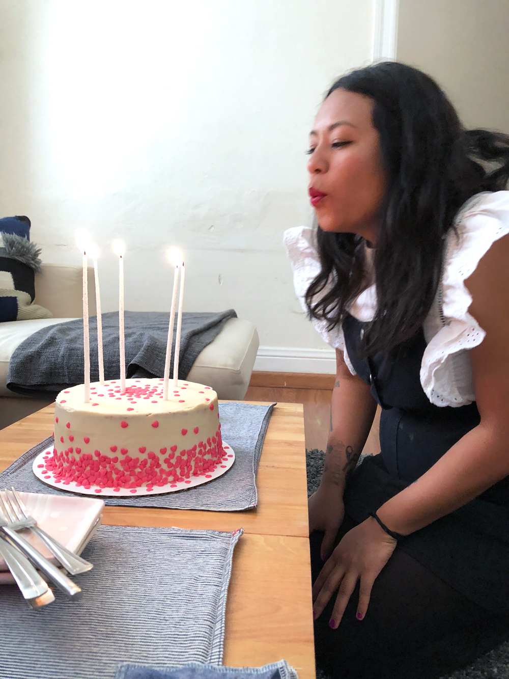 Pamela blowing out her birthday candles on her vegan pink funfetti birthday cake