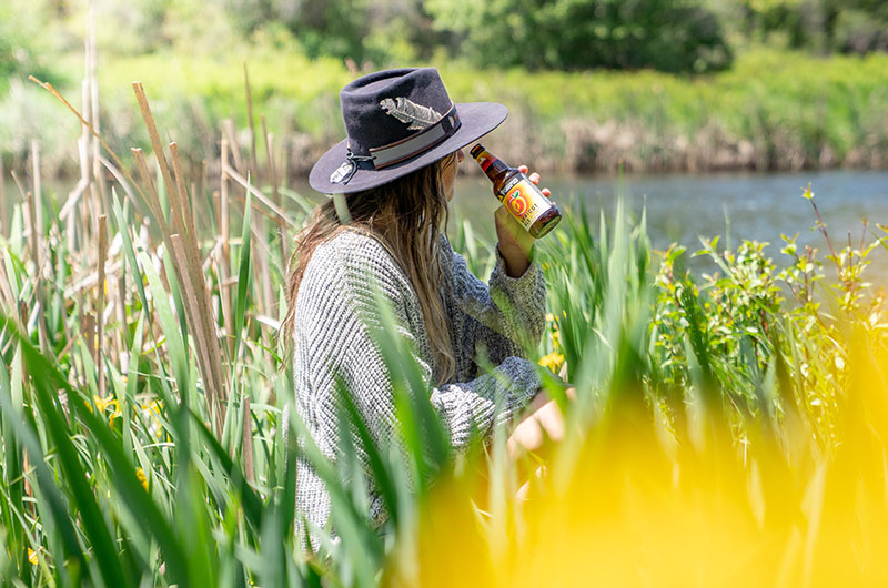 A woman in tall grass along the Deschutes River holding up a bottle of Apricot Ale