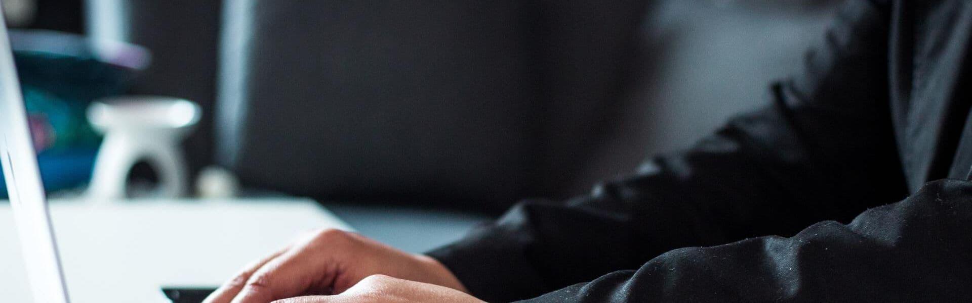 Hände von Kursteilnehmer schreiben auf Laptop während einer Live-Online-Schulung in Access