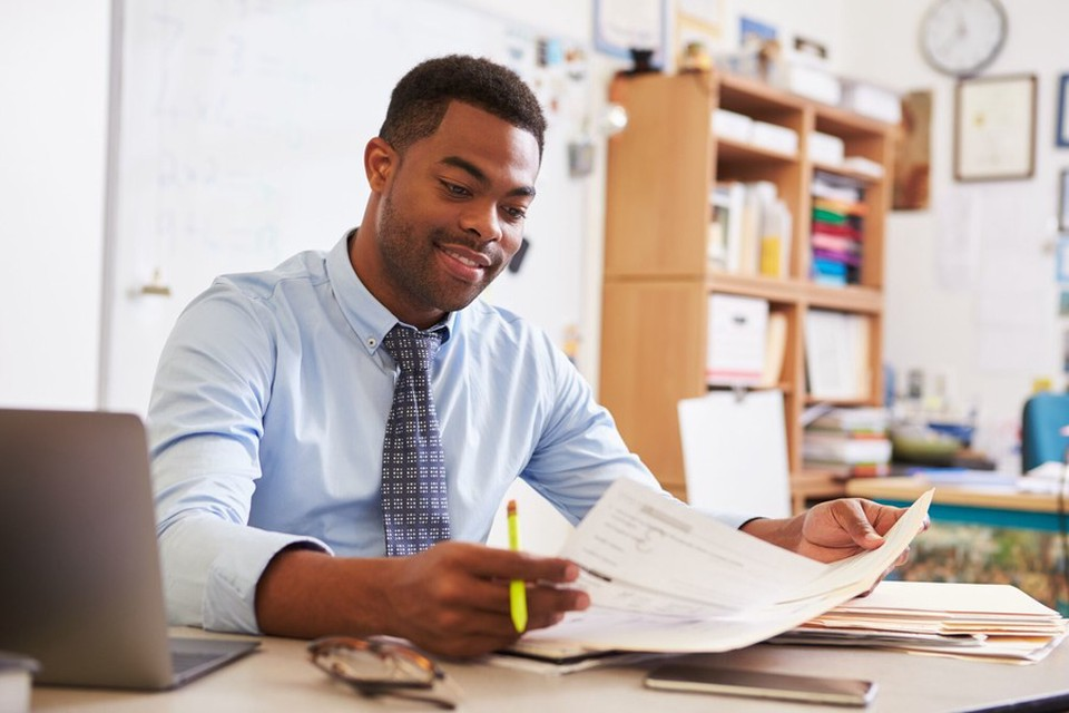 A man looking at a sheet of paper and smiling
