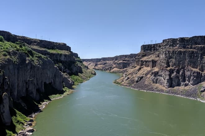 A desert river winds through a sheer canyon of dark volcanic rock. The left-side canyon wall is composed of noticeably lighter rock than the canyon wall on the right, and supports considerably more plant growth.