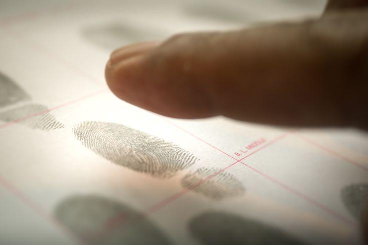 Finger putting inked fingerprints on paper