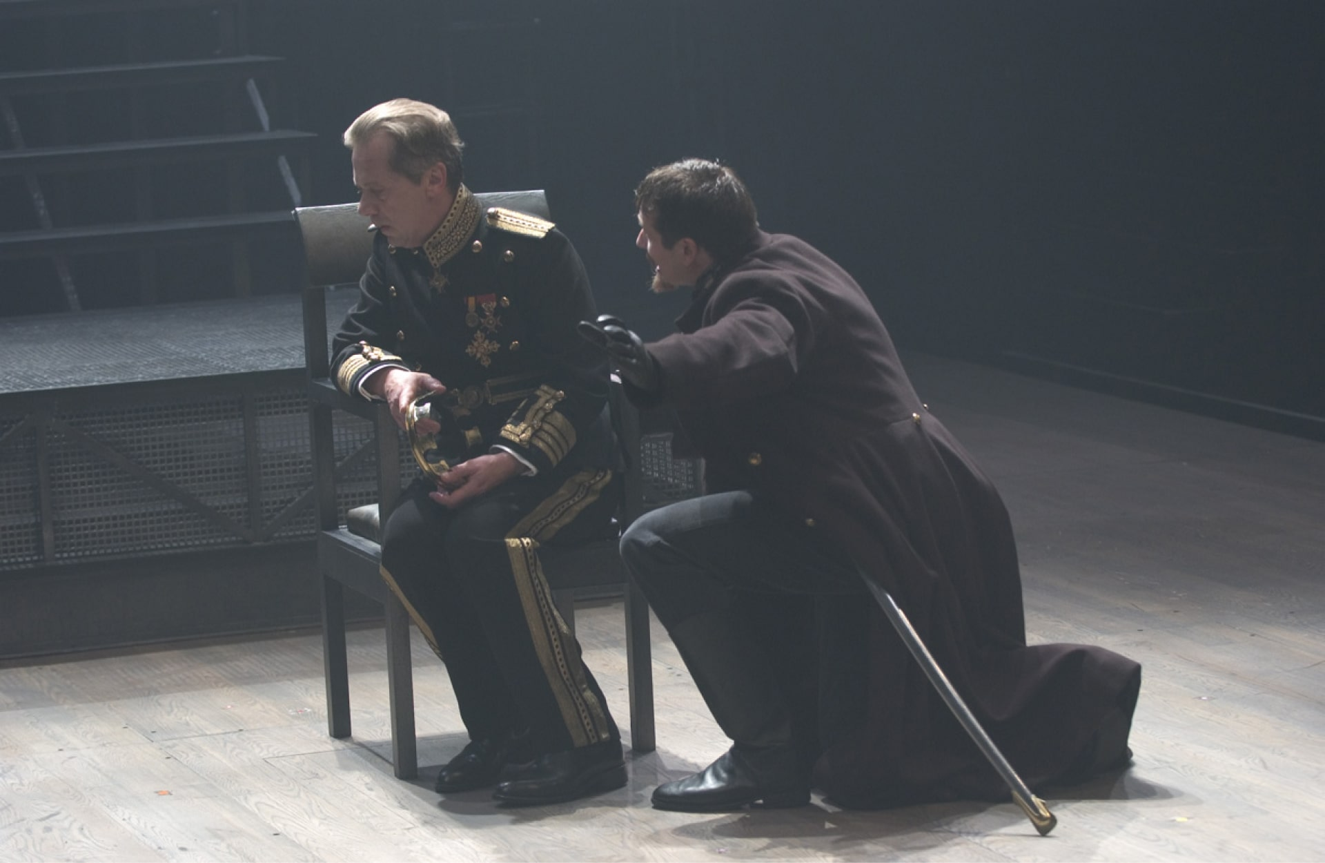 King sits on chair with man kneeling, in strong back light.