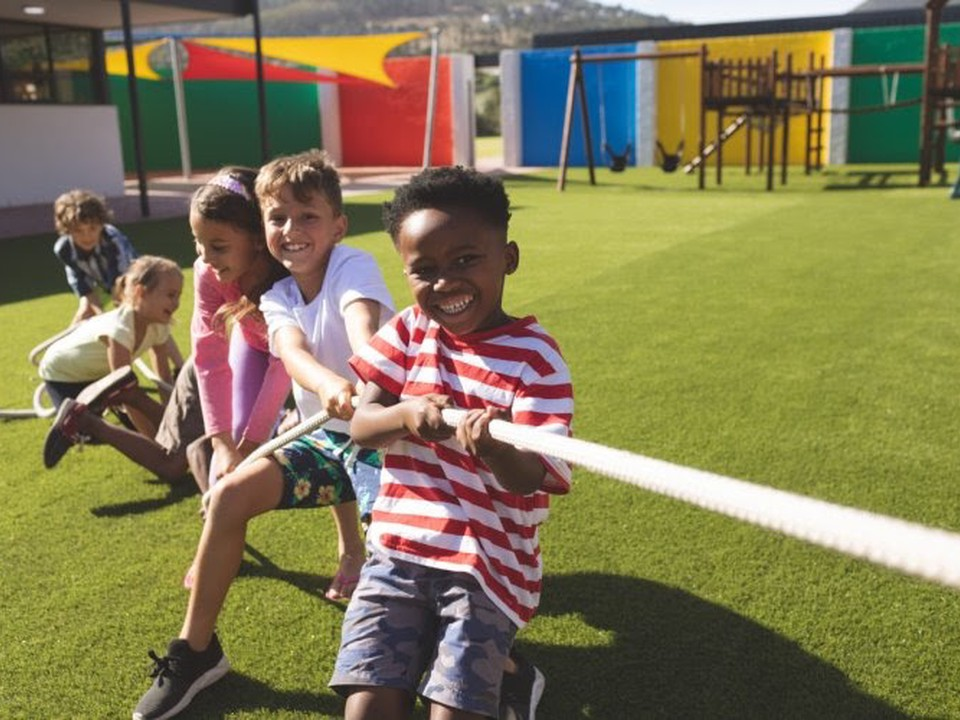 A group of smiling elementary school children play tug of war on the school playground in the summer.