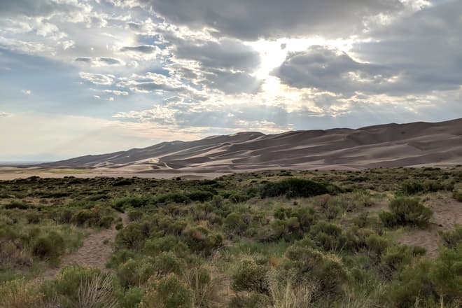 High desert scrubland ends abruptly in a field of high sand dunes. Near the center of the image, crepuscular rays emerge from the clouds.