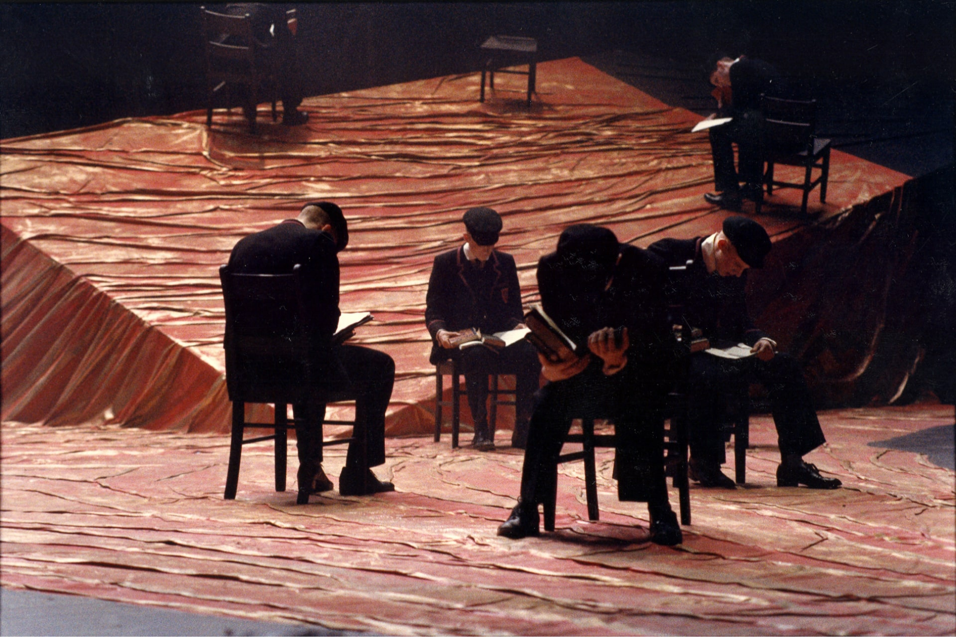 Uniformed schoolboys sit reading on chairs scattered on red fabric flooring.