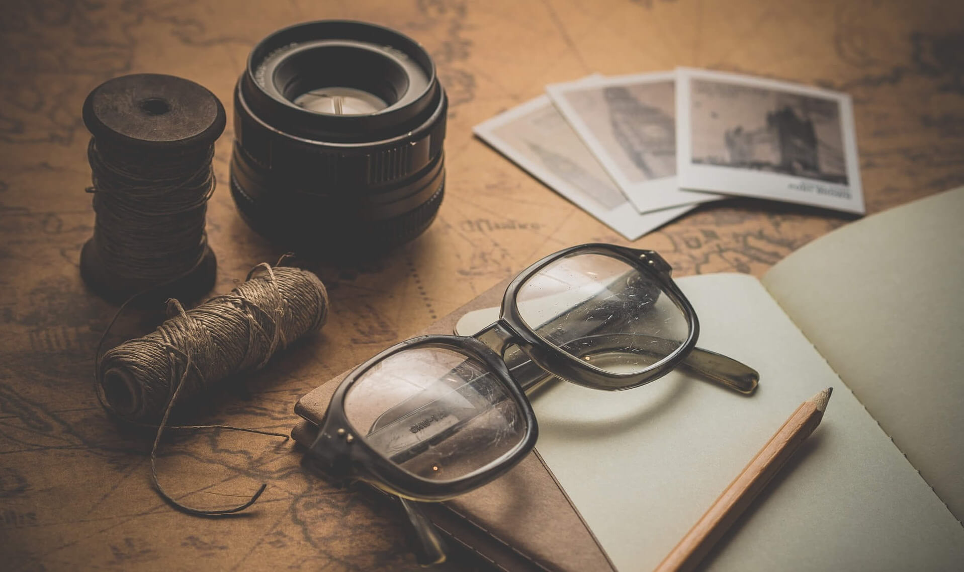 Planning A Vacation with glasses, diary, pencil, photographs, ropes and lenses