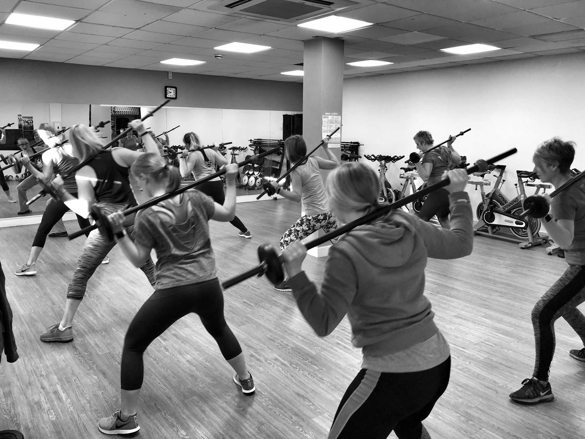 A black and white image of one of our fitness classes in Ashby. A group of women hold barbells with small weights over their shoulder in unison.