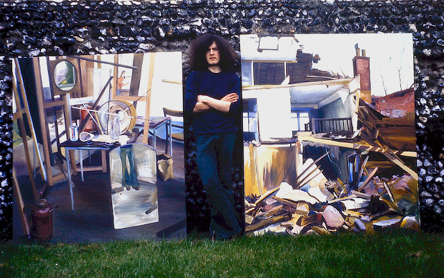 the artist photographed standing between two large paintings of a partially demolished house with detritus