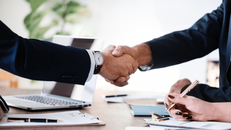 Business owner, client, colleague shakes hand across wooden desk with documents, paper, leaflets with perfect business advisor accountant and takes notes on paper with pen and on laptop #advisory