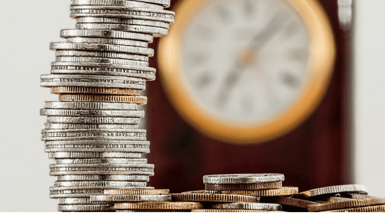 A pile of coins in focus in front of a clock on the wall as extra cash from existing clients #business