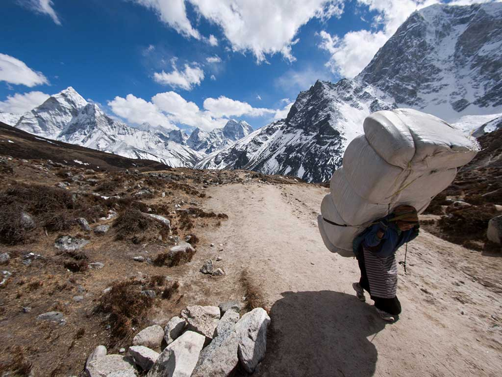 A Himalayan sherpa porter carries a large load uphill