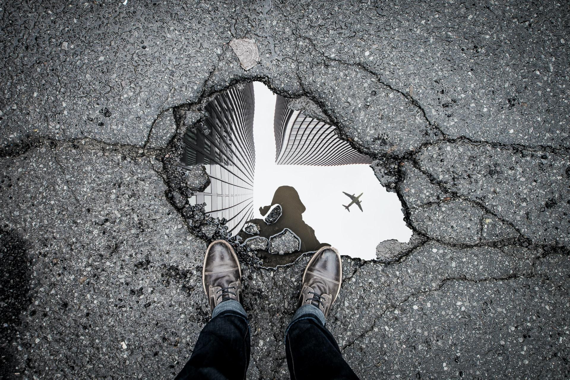 Poça de água em buraco na estrada com prédios no reflexo