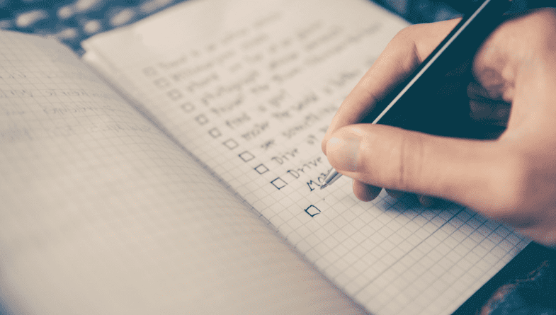 A person holding a pen ticking off a checklist on a notepad.