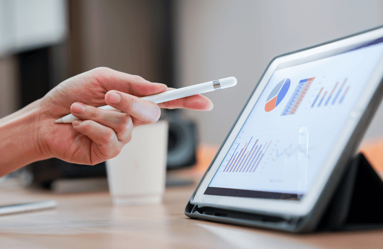 hand holding tablet pen pointing at tablet screen with graphs