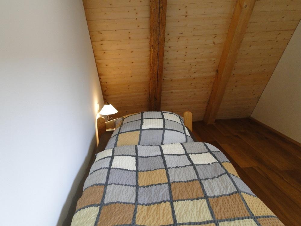 Einzelbett längs an der Wand mit Nachttisch am Kopfende