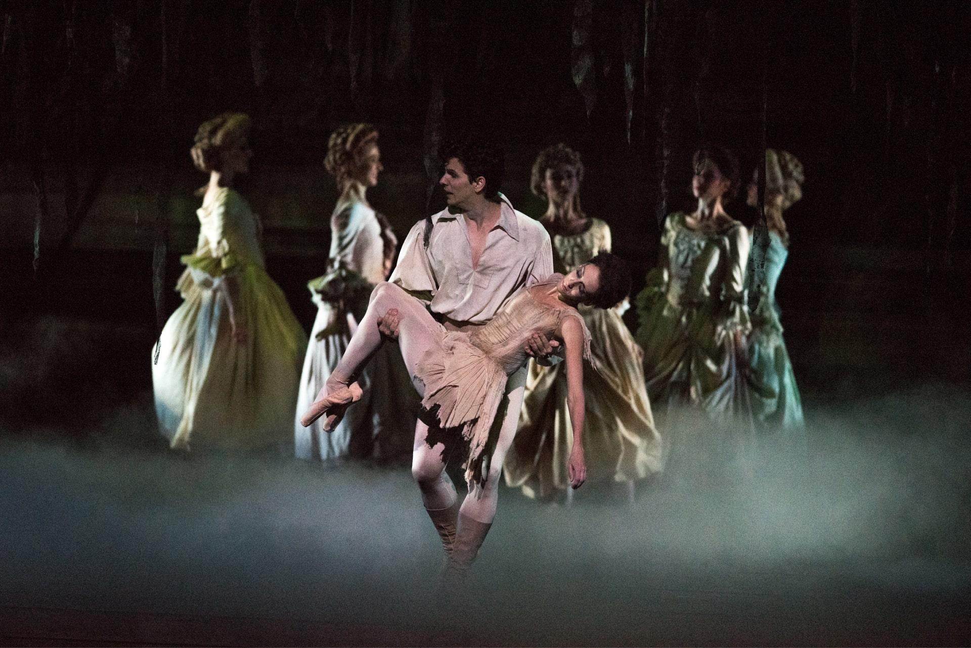 Dancer in white carries unconscious ballerina through dense fog away from elegant chorus.
