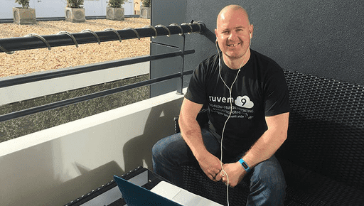 Niall McGinnity the owner of advisory firm Nuvem9 sits on a balcony at his home office in Portugal, made possible by cloud-working, wearing a branded t-shirt with Futrli on his laptop.