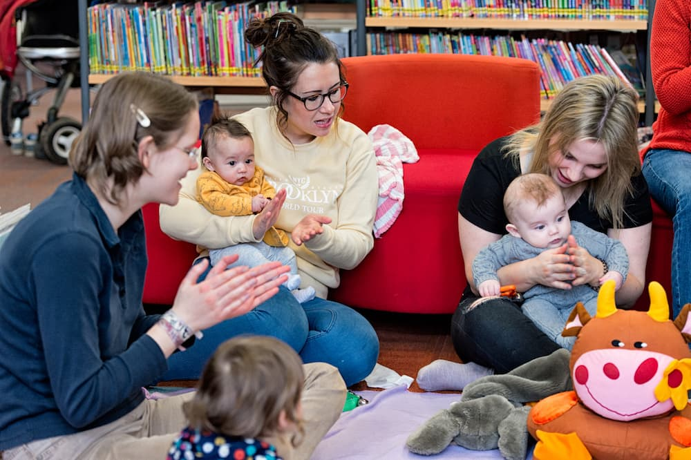 Parents and carers playing with babies in a library.