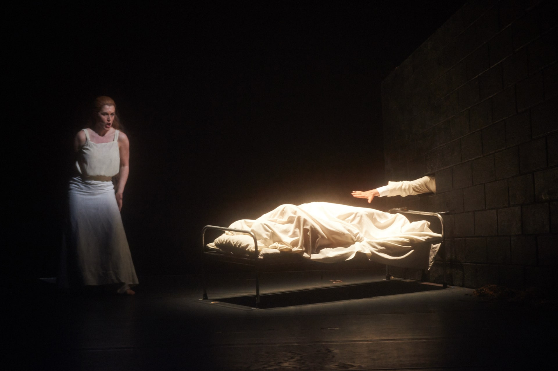 Woman in white camisole sings to shrouded body on iron cot as white-sleeved arm reaches out from brick wall.