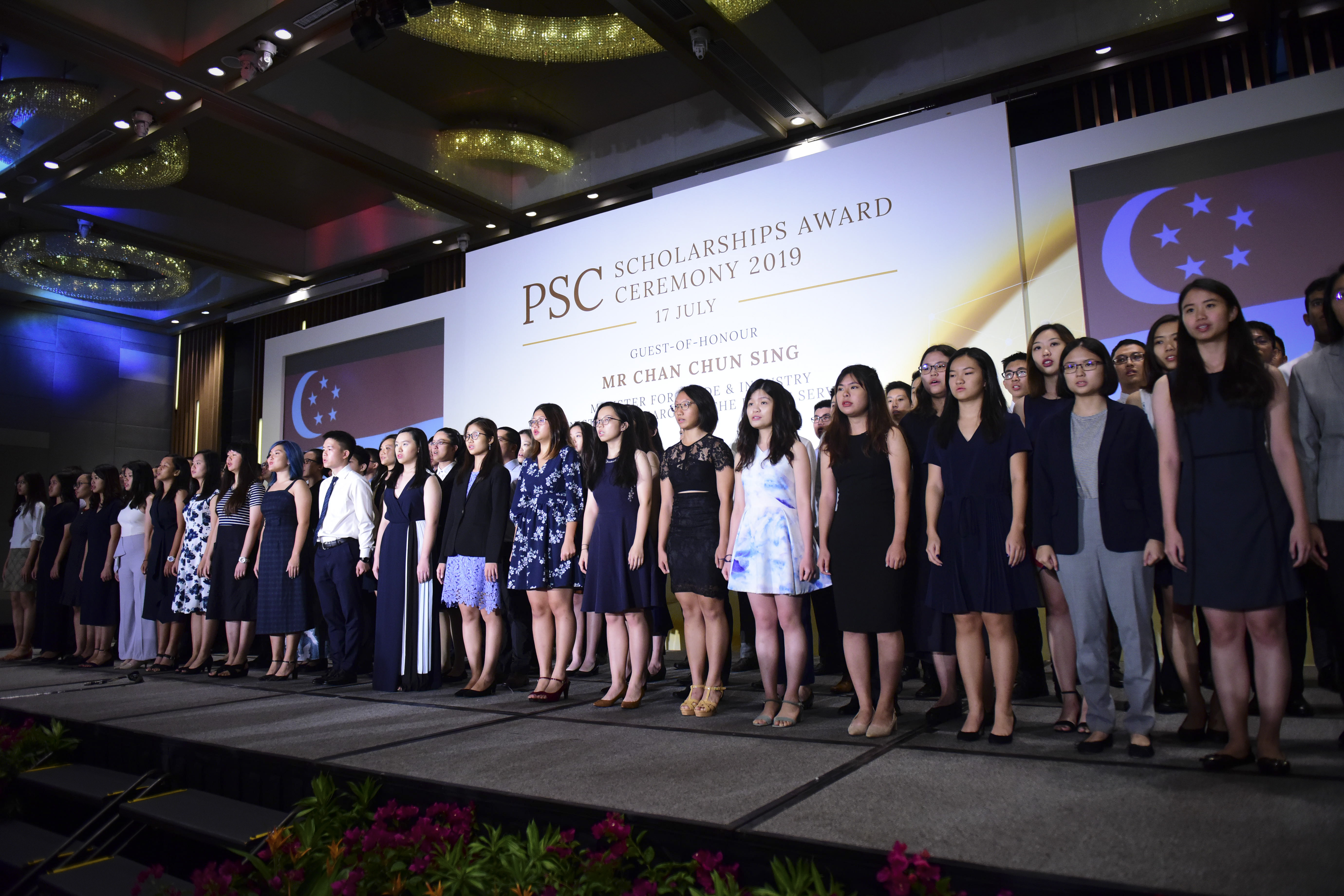 alt text - scholarship recipients singing national anthem at the 2019 PSC Scholarships Award Ceremony