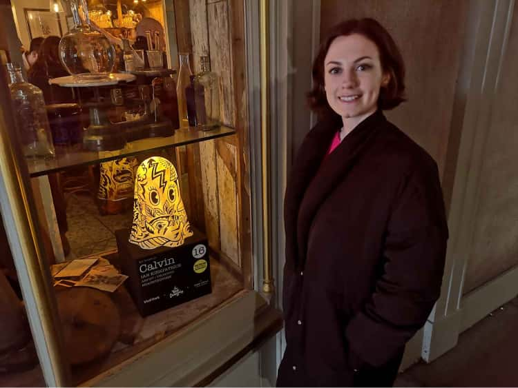 Naomi stood next to a shop window displaying a large lit up figure of a ghost for the York Ghost Hunt.
