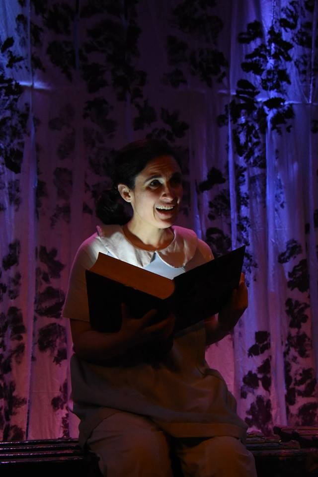 Photo of María Leigh (Iro) holding open a glowing book. From Custom Made Theatre Company's world premiere Of Serpants & Sea Spray production, 2016. Photo by Jay Yamada.