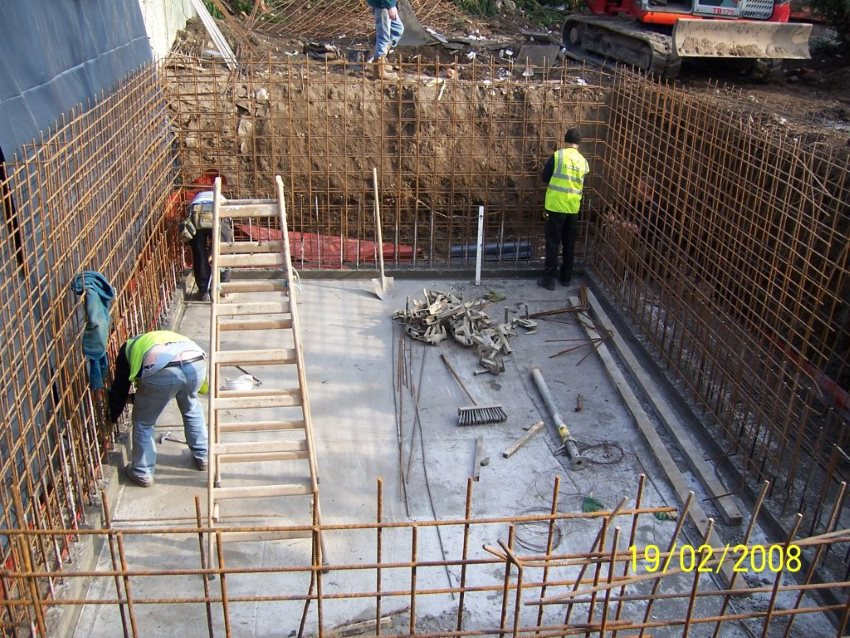 A photo showing three workmen in an approx. 10' deep hole with concrete floor and steel rebar in the walls (getting ready for the wall construction/pour).