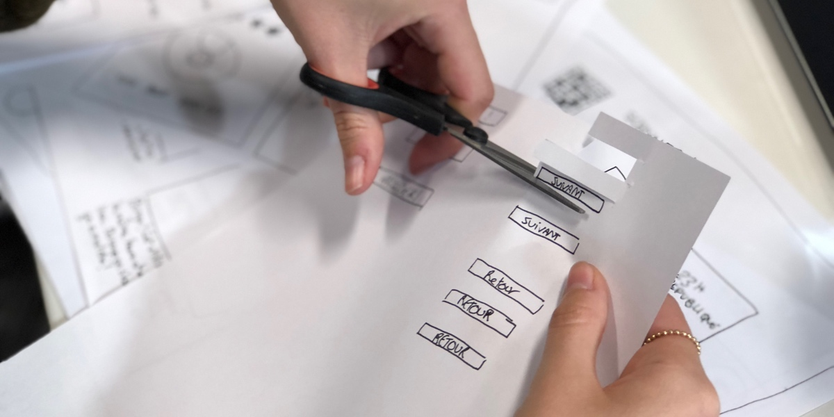 Close up of a UX designer's hands. They are cutting out elements for a paper prototype