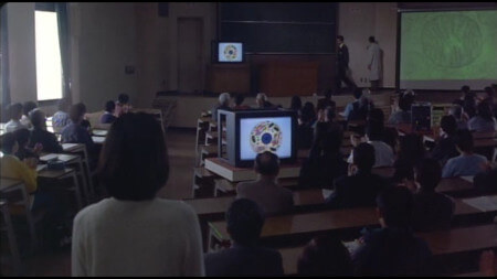 A packed lecture theatre, with Kiyomi looking on, as images of Mitochondria are shown