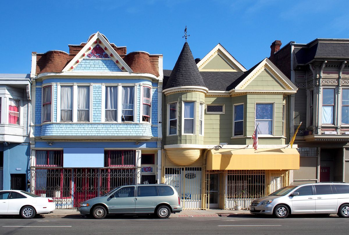 brightly painted homes and storefronts with varying roofing styles in oakland, california