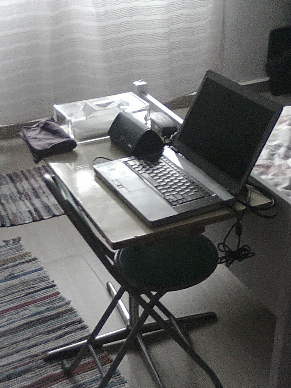 My desk in 2011: a very small table sitting at the bottom edge of my old bed, an old laptop with a broken speaker, and an external speaker sitting next to it. The chair was a foldable beach chair.