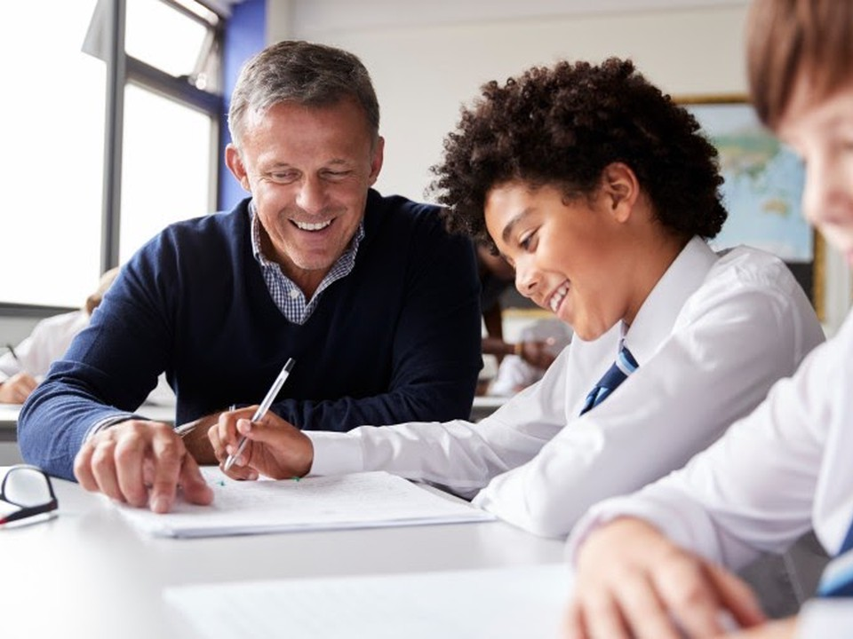 Teacher helps a smiling student wearing a school uniform.