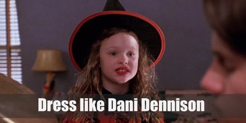 Dani dresses up as a witch for Halloween, which is very timely since her family just moved to Salem. She wears a black turtleneck long-sleeved top, black skirt, red poncho, and a pointed witch's hat.