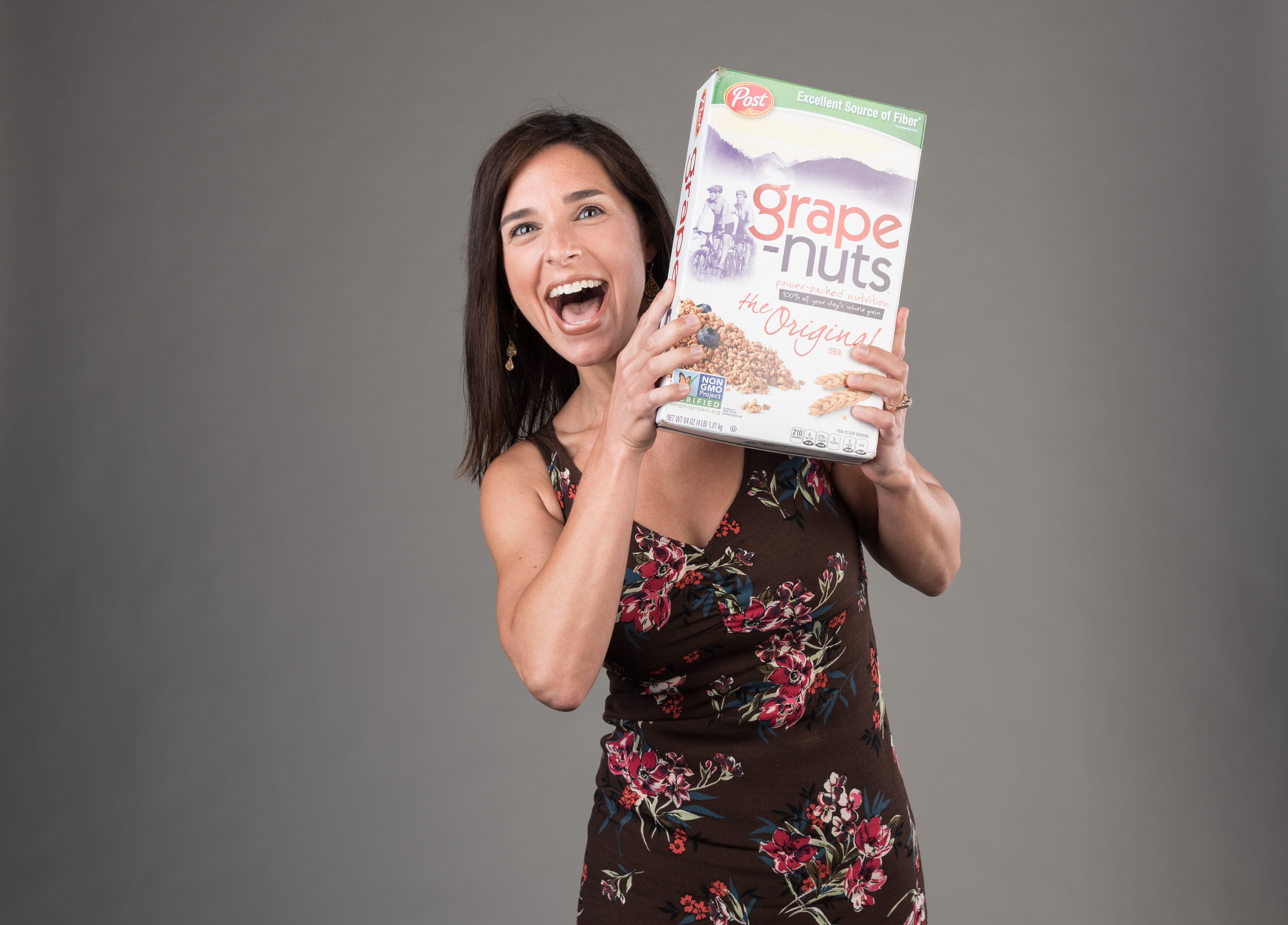 Portrait of woman holding cereal box