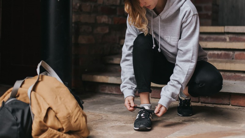 A pupil in a heather grey leavers hoodie tying her shoelace