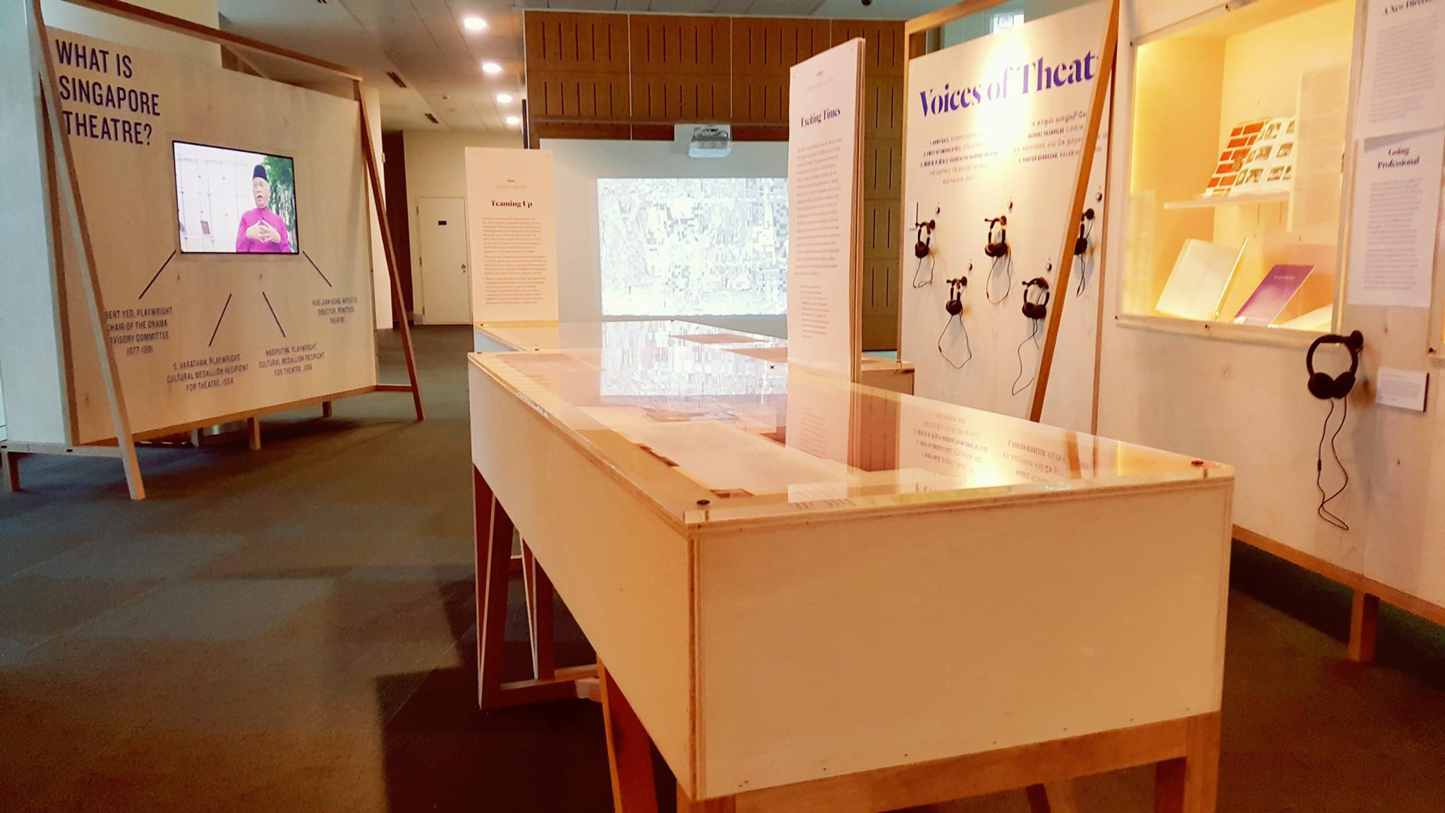 A table showcase is in the middle. On the left, there is a wall with a TV screen, showing a video. On the right wall, there is a wall showcase and several headphones for playing sound samples.