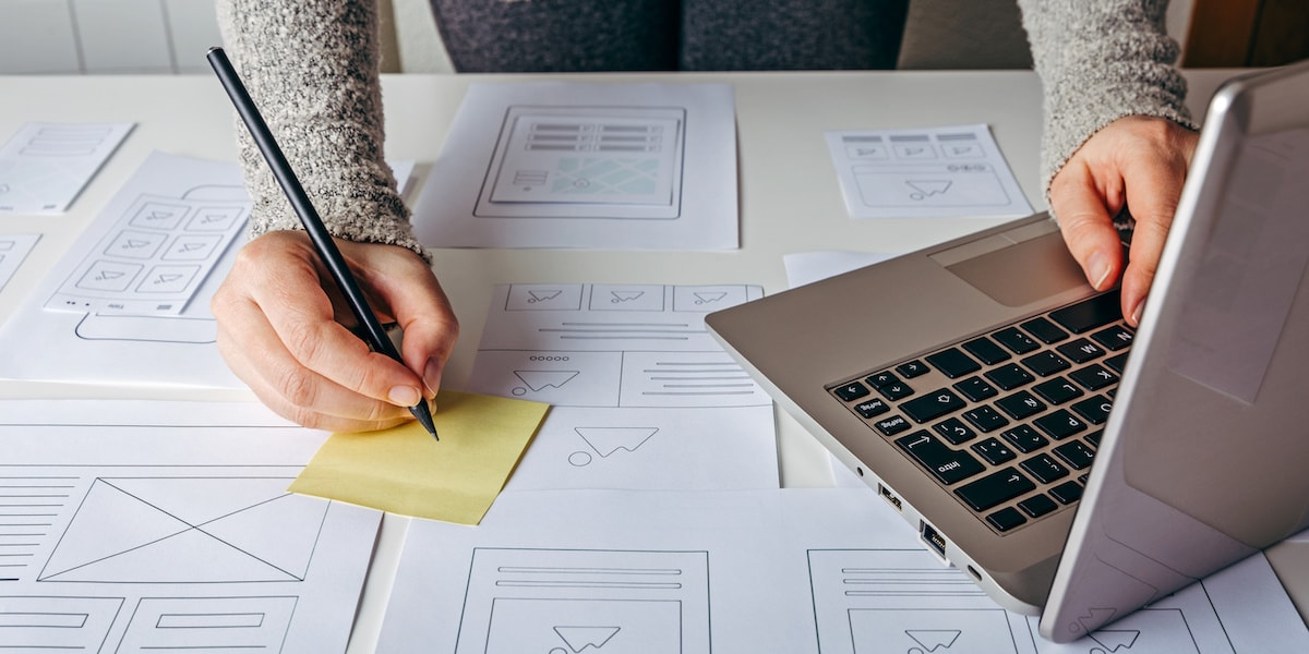 UX designer making notes and typing on his laptop