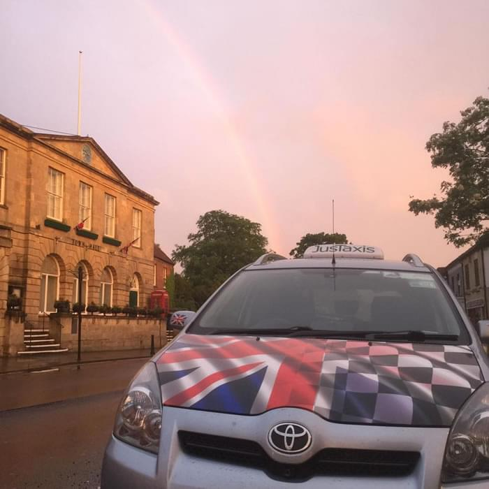 JusTaxis Taxi picking up at Glastonbury Town Hall in Somerset