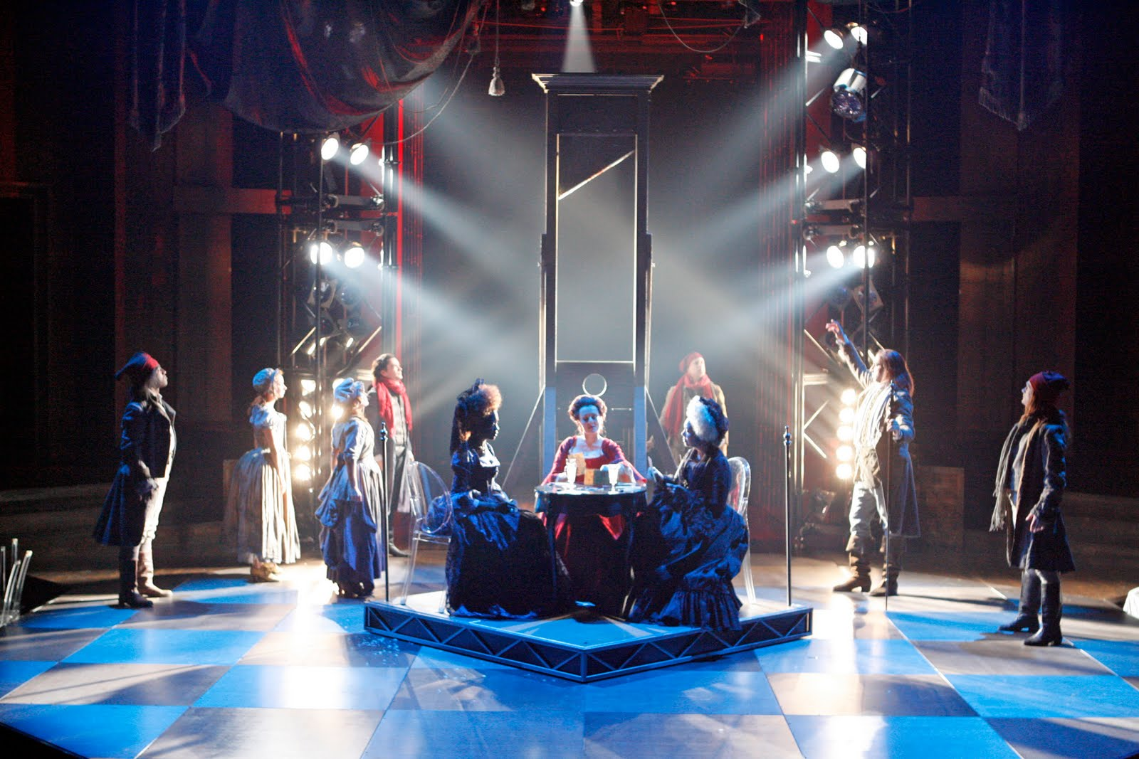 Three women play cards in front of brightly light guillotine on checkered stage.