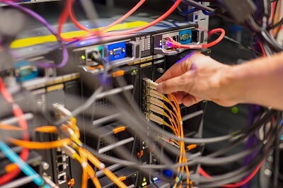 A technician performing maintenance on fiber optic cables connecting to a server.