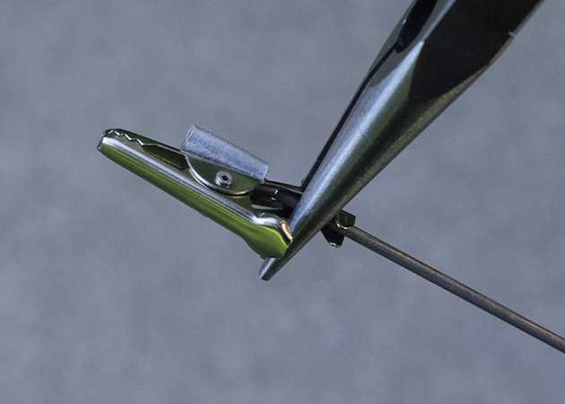 Needle Nose Pliers Squeezing Alligator Clip Around Music Wire