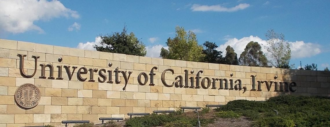 UC Irvine sign on stone with blue skies in the background