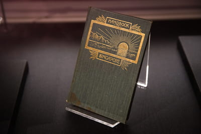 A dark green book is propped up, and its title and illustration is gilded in gold leaf. The title is 'Handbook to Singapore'. The illustration is of a sun halfway in the sea, with mountains on the side.