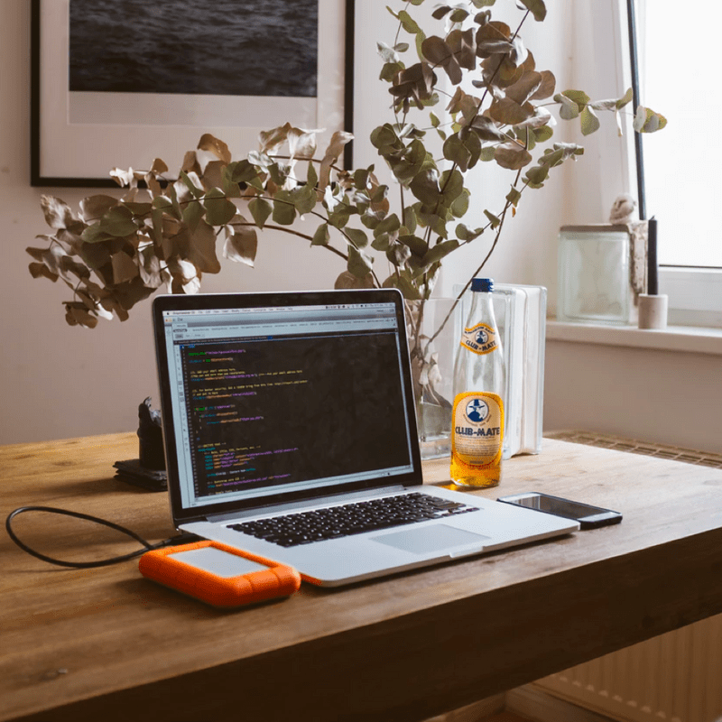 Laptop on desk with drink