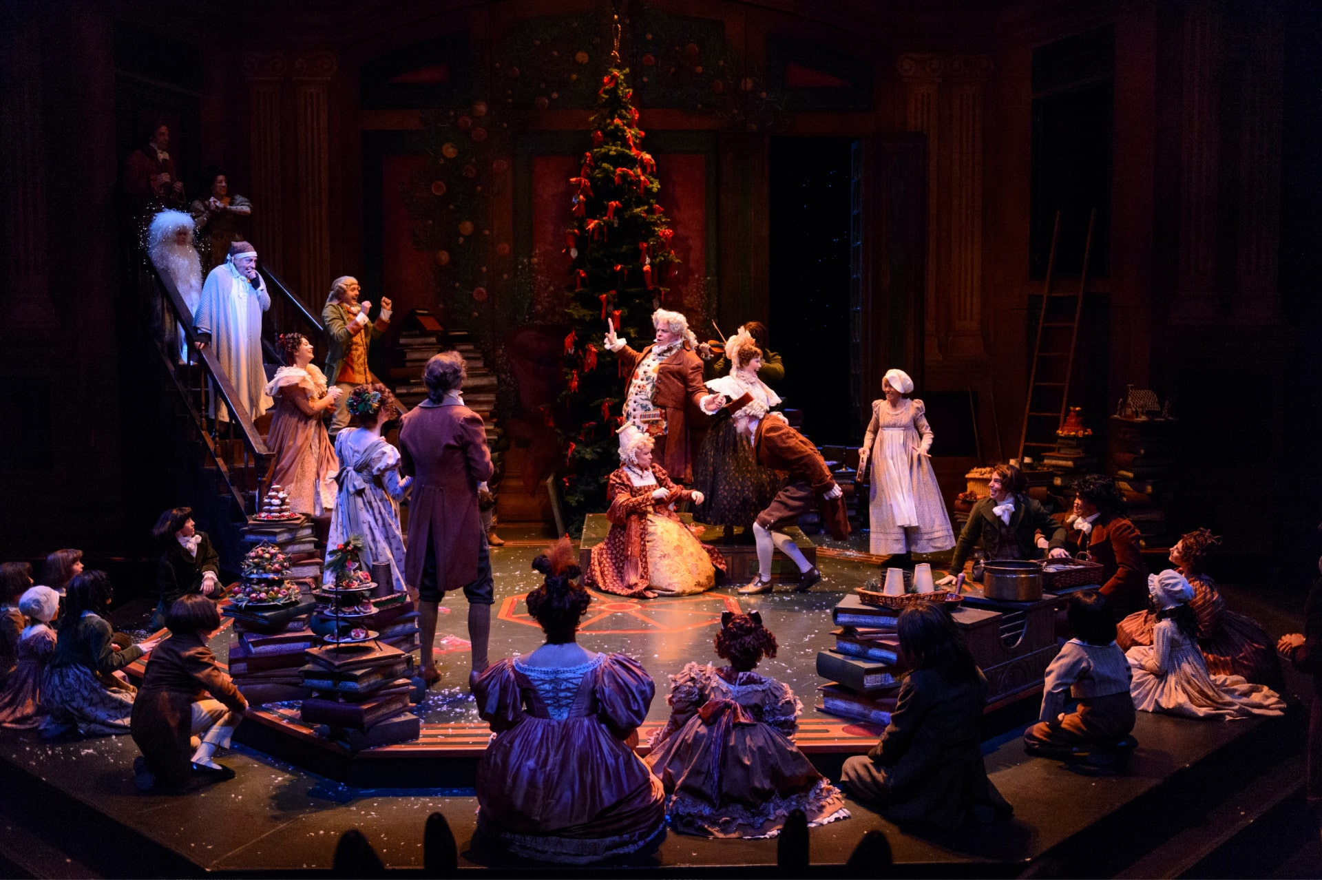 Victorian partygoers rejoice at Christmas tree in warm light.