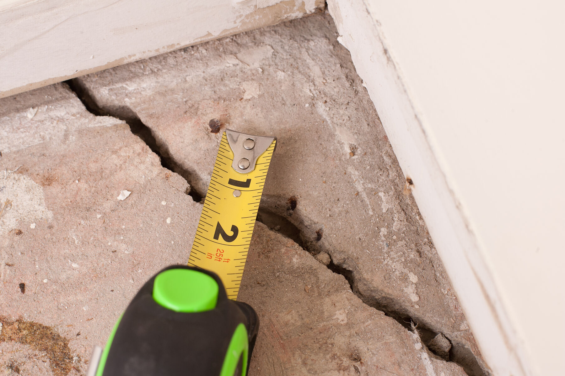 ruler measuring a cracked concrete floor
