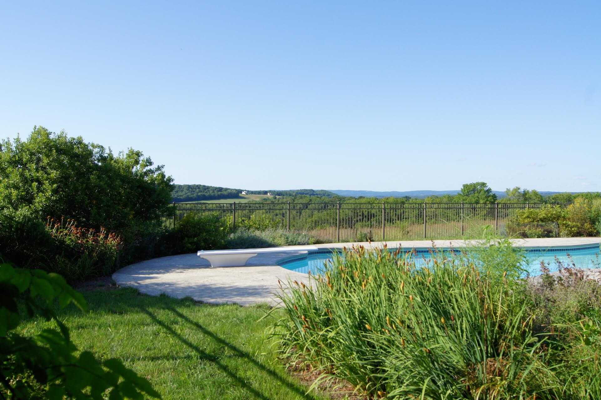 facing the meadow past the pool and landscape